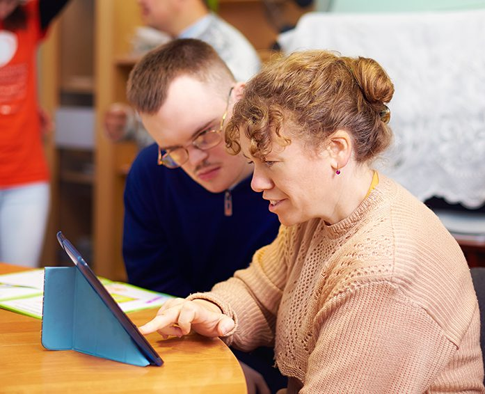 NDIS participant and his carer look at Ipad together